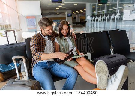 Joyful loving couple is waiting at the airport. They are sitting and reading their tickets with interest. Man and woman are embracing and smiling