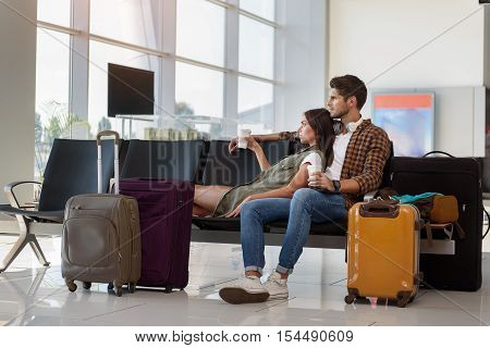Far from home. Pensive young man and woman are waiting for flight at airport. They are sitting near suitcases and drinking coffee. Lovers are embracing and looking forward with sadness