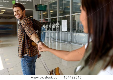 Goodbye. Young woman is seeing off her boyfriend in airport. They are holding hands and smiling