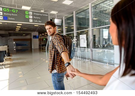 Do not go. Young woman is holding male hand and begging. Man is standing with suitcase at airport and looking at her with surprise