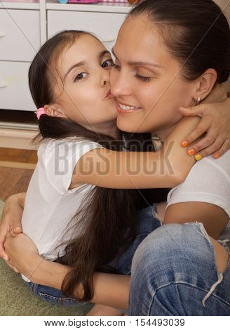 daughter the teenager kisses mother on a cheekdressed in white undershirts sit in a nursery