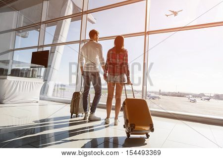 Cute loving couple is watching flight and sunset at airport. They are standing near window and carrying suitcases