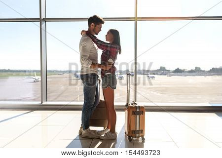 We are ready for new future. Young man and woman are standing near window of airport and embracing. They are looking at each other with love