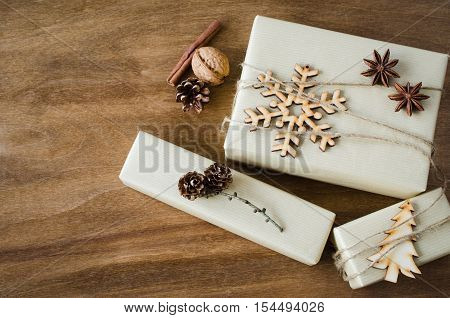 Vintage Kraft Gift Box Decorated with Wooden Snowflake Pine Cones Star Anise and Xmas Tree on Wooden Background. Christmas in Rustic Style. View from above with copy space.