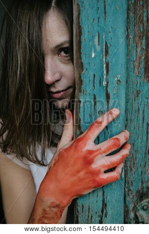 Ghost woman behind vintage wooden door, blood covered hand