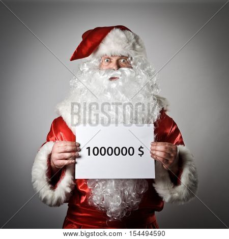 Santa Claus is holding a white paper in his hands. One million dollars concept.