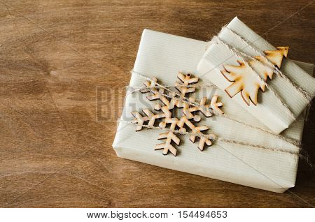 Kraft Boxes with Gifts Decorated with Wooden Snowflake Christmas Tree and Jute on Wooden Background. Christmas in Rustic Style. View from above with copy space.