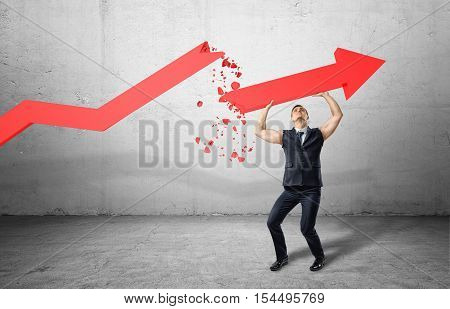An athletic businessman full-height in a jacket without sleeves holding up a big red arrow pointing up, all on the grey background. Business and management. Power and confidence. Way to success.