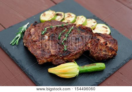 Rib eye steak on black slate plate