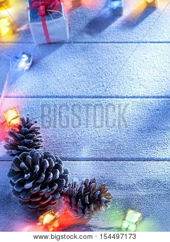 close up view  of  cones and gift box on snowbound  wooden back