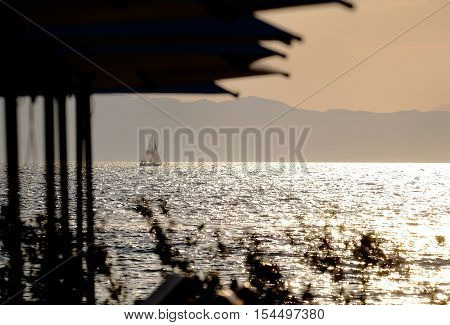 a sailing boat in the distance at sunset
