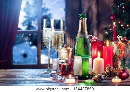 close up view of champagne with candles and gifts on color back