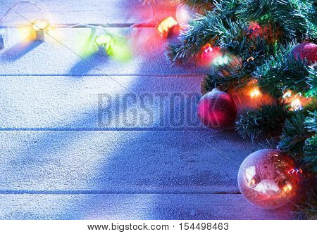 close up view  of lit Christmas tree on snowbound  wooden back