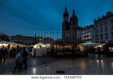 Krakow Poland - October 2 2016: The old city of Krakow the main square of St. Mary's Church and historic houses in the early evening