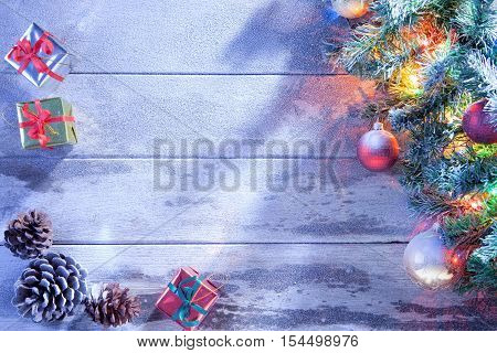 view  of lit Christmas tree  and gift boxes on snowbound  wooden back