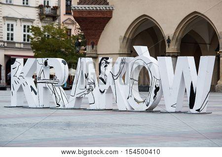 Krakow Poland - October 27 2016: Krakow sign in large white capital letters on Rynek Glowny the old city market square.