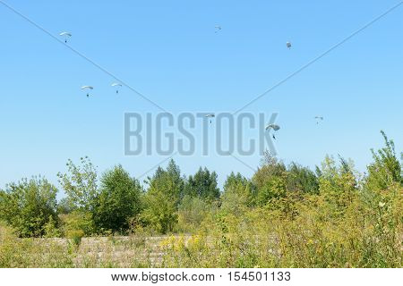 Paratroopers descend to earth on the blue clear sky background