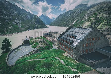 Great view from the top of the Grimsel pass over the Grimselsee hotel and dam. Switzerland, Bernese Alps, Europe. Toned like Instagram filter
