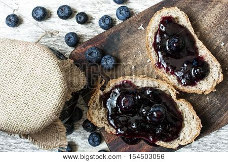 bread with homemade blueberry jam on a white rustic table and jam in a jar with fresh berries. top view