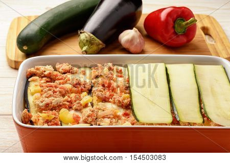 Casserole with chicken, eggplant, zucchini and tomatoes. Cooking process.