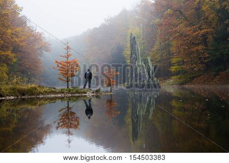 Traveler near Rakotzbruecke (Devil's bridge) in early morning mist, in autumn, Kromlau, Germany