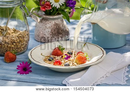 Oatmeal with fruit and milk on old wooden table