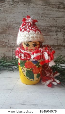 Winter scene with nesting doll in a knitted cap and scarf on wooden background
