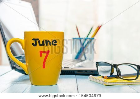 June 7th. Day 7 of month, color calendar on morning coffee cup at business workplace background. Summer concept. Empty space for text.
