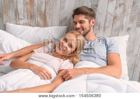 Happy married life. Joyful young man and woman are lying in bed and hugging. They are smiling