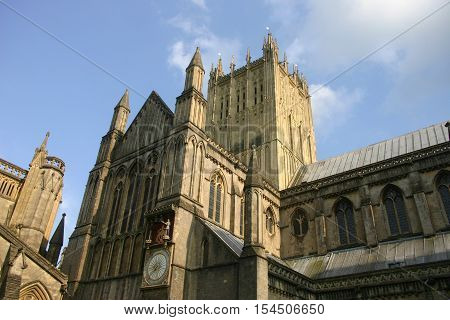 The upper part of the north side of Wells Cathedral Somerset showing the mediaeval clock. Background of blue sky with white clouds.