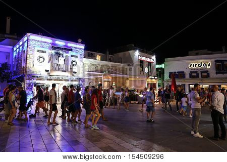 MUGLA TURKEY - SEPTEMBER 11 2016: People in Bodrum bar street at night. Bodrum bar street is one of the most famous nightlife district in Turkey.