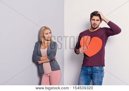 What I have done. Young man is holding torn heart and touching head with regret. Young woman is standing and looking at him with offence