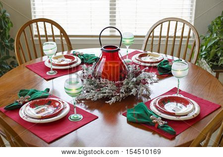Christmas Holiday Dining Dinner Setting Arrangement Table. Christmas dinner set for four on the round table lit by morning light. Christmas interior design.