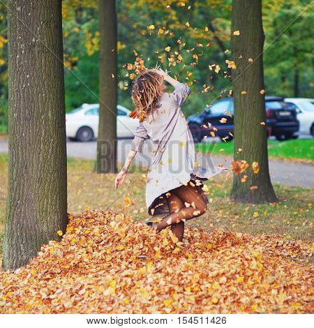 Elegant petite girl has fun whirling and tossing leaves in the air in a St. Petersburg yard clear autumn day.