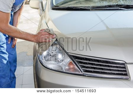 The worker polishes optics of headlights of the car to restore gloss and transparency poster