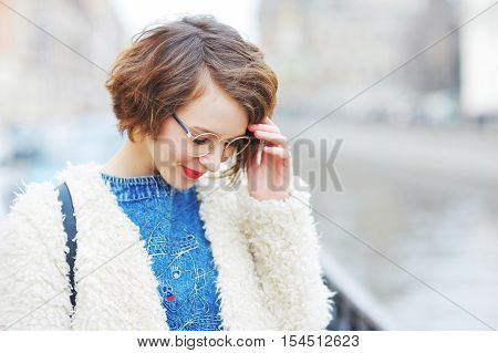 Portrait of a shyly smiling young woman in glasses on a city street close-up