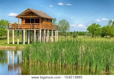 summer landscape. one of the backwaters of the Tisza (Tisa) river in Tiszalok, Hungary. yellow stilt house. hungarian countryside.