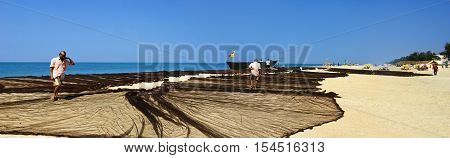 GOA, INDIA - NOVEMBER 20, 2012: Unidentified fishermen dry an old fisher's net. Beaches in Goa are state-owned so the hotels do not have the right to prohibit boats and nets drying on the beaches.
