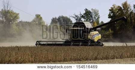 Brockville, ON, October 7, 2016 -- Close up of large yellow combine harvester clearing and seeding a grain field near Brockville, Ontario, on a bright sunny cloudless day in October