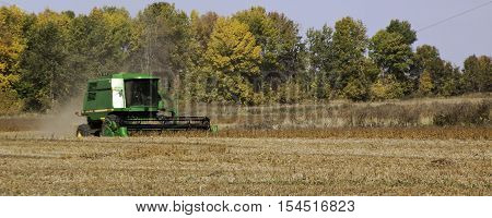 Brockville ON October 7 2016 -- Wide view of large green combine harvester clearing and seeding a grain field near Brockville Ontario on a bright sunny cloudless day in October