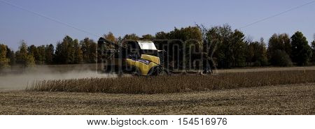 Brockville, ON, October 7, 2016 -- Wide side view of large yellow combine harvester clearing and seeding a grain field near Brockville, Ontario on a bright sunny cloudless day in October