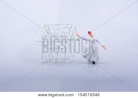 Sufi dervish and a little metal house on a white background