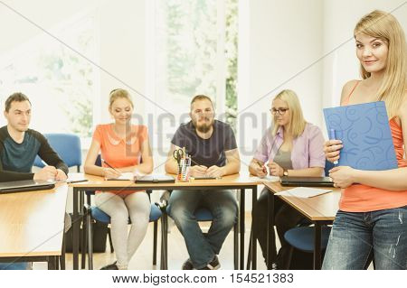Education high school teamwork and people concept - smiling student girl with notebook standing in front of students her group mates in classroom