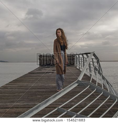 Caucasian girl at the old ruin berth turning back at sea cloudy day. Melancholy concept