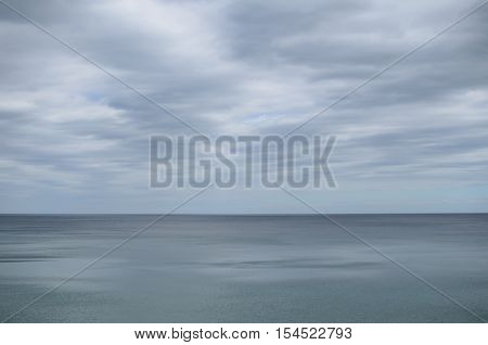 Pale cloudy sky over dim greyish sea water