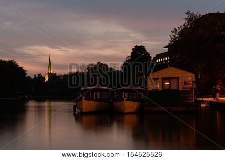 STRATFORD-UPON-AVON UK - OCTOBER 30 2016  Cruise boats at night on the River Avon. Vessels for tours rock slowly on the water after dark with spire of Holy Trinity Church