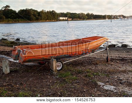 Colorful old orange boat tender on a trolley by a public slipway on a cloudy day. poster