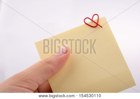 Hand Holding A Note Paper With Heart Shaped Clip