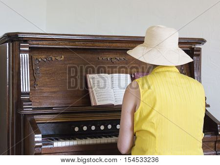 horizontal image of a caucasian woman playing hymns on an antique old pump organ.
