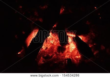 Charcoal or coal burning red hot in a furnace, camp fire or fire pit.